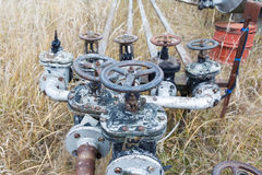 Old rusty pipes and tanks. Old rusty pipes and oil valve, yellow grass at an abandoned oil refinery Stock Photography