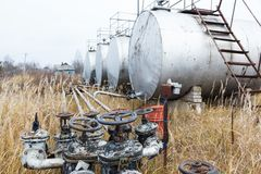 Old rusty pipes, valves and tanks. At an abandoned oil refinery Stock Photography