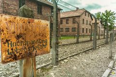 Old rusty plate warning sign indicating electric fence with barbed wire at The Nazi concentration camp of Auschwitz in royalty free stock photos