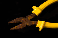 Really old rusty pliers. With yellow on black background Royalty Free Stock Photography
