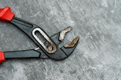 Old and rusty plumbing pliers on concrete floor royalty free stock images