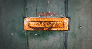 Old rusty Portuguese mailbox on a worn wooden door royalty free stock photography