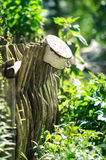 Old Rusty Pot On The Fence. Old rusty pot with ears hanging on railing of wooden fence Royalty Free Stock Photo
