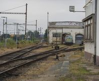 Old rusty railway station with train depot and rail tracks Royalty Free Stock Image
