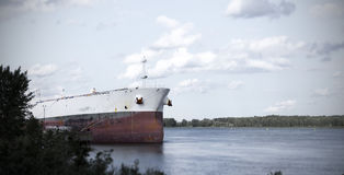 Old rusty red and white cargo ship waiting for unload stock photography