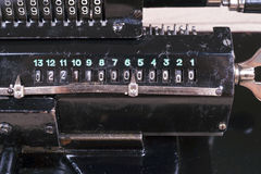 Old rusty retro calculator black standing on a wooden table Stock Photo
