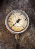 Old rusty round industrial pressure gauge with numbers round the dial. Mounted on a metal surface of a large abandoned diesel powered generator stock photography