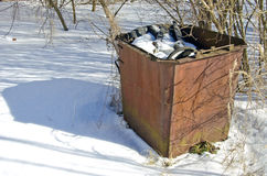 Old rusty rubbish container on snow Royalty Free Stock Image