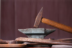 Old rusty rugged anvil, hammer and other blacksmith tools. Stock Image