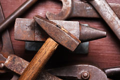 Old rusty rugged anvil, hammer other blacksmith tools. Royalty Free Stock Photography