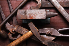 Old rusty rugged anvil and other blacksmith tools. Royalty Free Stock Photos