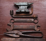 Old rusty rugged anvil and other blacksmith tools. Stock Image