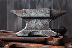 Old rusty rugged anvil on top of other blacksmith tools. Stock Images