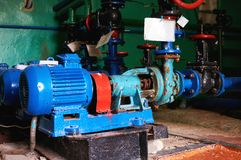 Old, rusty and scratched water pump with an electric motor painted in blue on the cold water pipeline. royalty free stock photography