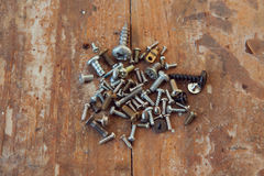 Old rusty screws bolts on the wood texture closeup. Screws bolts cloves on a wooden closeup royalty free stock image