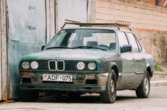 Old rusty sedan car BMW 3 Series, E30, parking on street. The BMW. Tbilisi, Georgia - October 21, 2016: Old rusty sedan car BMW 3 Series, E30, parking on street Royalty Free Stock Image