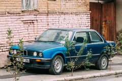 Old rusty sedan car BMW 3 Series, E30, parking on street. The BMW. Tbilisi, Georgia - October 21, 2016: Old rusty sedan car BMW 3 Series E30 parking on street Stock Images