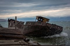 Old, rusty ship near the pier. Big waves flood the deck. Summer cloudy evening royalty free stock images