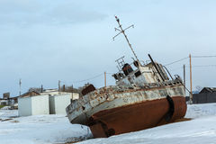 Old rusty ship on winter shore of Lake Baikal. Royalty Free Stock Image