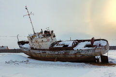 Old rusty ship on winter shore of Lake Baikal. Royalty Free Stock Photography