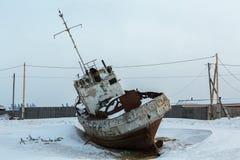 Old rusty ship on winter shore of Lake Baikal. Stock Photos