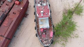 Old rusty ships on the riverbank on the sand. Aerial filming