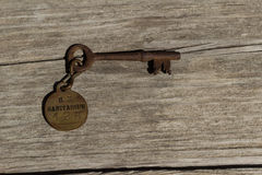 Old rusty skeleton key to a sanitarium. / mental hospital on a wood bench stock images