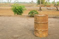 Old rusty steel drum at outdoor farm. In rural royalty free stock image