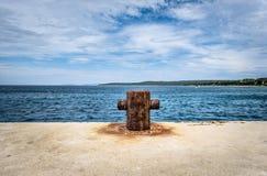 Old rusty steel mooring bollard pole on a pier. Royalty Free Stock Photos