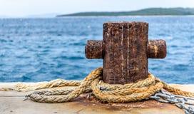 Old rusty steel mooring bollard pole on a pier. Stock Photos