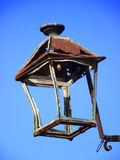 Old and rusty street lamp. Pending against blue sky stock photography
