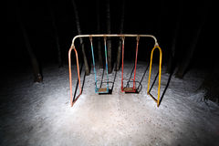 Old rusty swing stand in dark park Royalty Free Stock Image