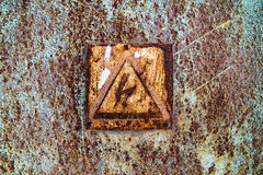 Old rusty tin surface with warning sign of high voltage Stock Photo