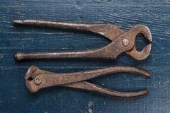 Old rusty tongs on blue table Stock Images