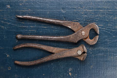 Old rusty tongs on blue table Stock Photos