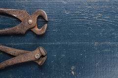 Old rusty tongs on blue table Royalty Free Stock Photo