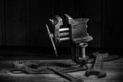 Old rusty tool in the dark room, totally dark place, playing with lights, old stuff, vice, keys on wooden table, black and white p. Hoto stock images