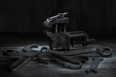 Old rusty tool in the dark room, totally dark place, playing with lights, old stuff, vice, keys on wooden table, black and white p. Hoto royalty free stock photography