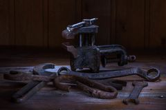 Old rusty tool in the dark room, totally dark place, playing with lights, old stuff, vice, keys on wooden table.  royalty free stock photo
