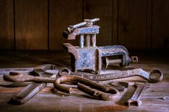 Old rusty tool in the dark room, totally dark place, playing with lights, old stuff, vice, keys on wooden table, black and white p. Old rusty tool in the dark royalty free stock images