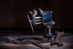Old rusty tool in the dark room, totally dark place, playing with lights, old stuff, vice, keys on wooden table, black and white p. Old rusty tool in the dark royalty free stock photos