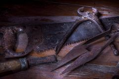 Old rusty tool in the dark room, totally dark place, playing with lights, old stuff, vice, keys on wooden table, black and white p. Old rusty tool in the dark royalty free stock image