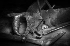 Old rusty tool in the dark room, totally dark place, playing with lights, old stuff, vice, keys on wooden table royalty free stock photo