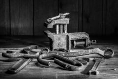 Old rusty tool in the dark room, totally dark place, playing with lights, old stuff, vice, keys on wooden table, black and white p. Hoto royalty free stock photo