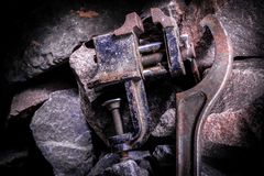 Old rusty tool in the dark room, totally dark place, playing with lights, old stuff, vice, rock.  royalty free stock photo
