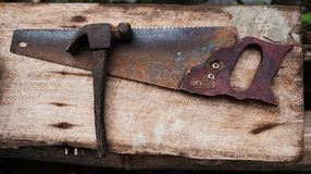 Old rusty tools hammer and hand saw for work. Old rusty tools hammer and hand saw for carpenter work royalty free stock photography