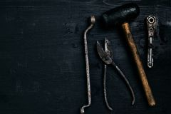 Old, rusty tools lying on a black wooden table. Hammer, chisel, metal scissors, wrench. Top view. Copy space. Still life. Flat lay royalty free stock photo