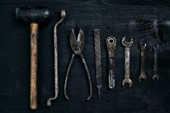 Old, rusty tools lying on a black wooden table. Hammer, chisel, metal scissors, wrench. Top view. Copy space. Still life. Flat lay royalty free stock photos