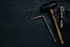 Old, rusty tools lying on a black wooden table. Hammer, chisel, metal scissors, wrench. Top view. Copy space. Still life. Flat lay royalty free stock photography