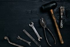 Old, rusty tools lying on a black wooden table. Hammer, chisel, metal scissors, wrench. Top view. Copy space. Still life. Flat lay royalty free stock images